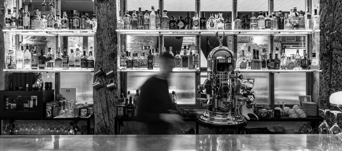 Un camarero sirve bebidas tras la barra de un bar.