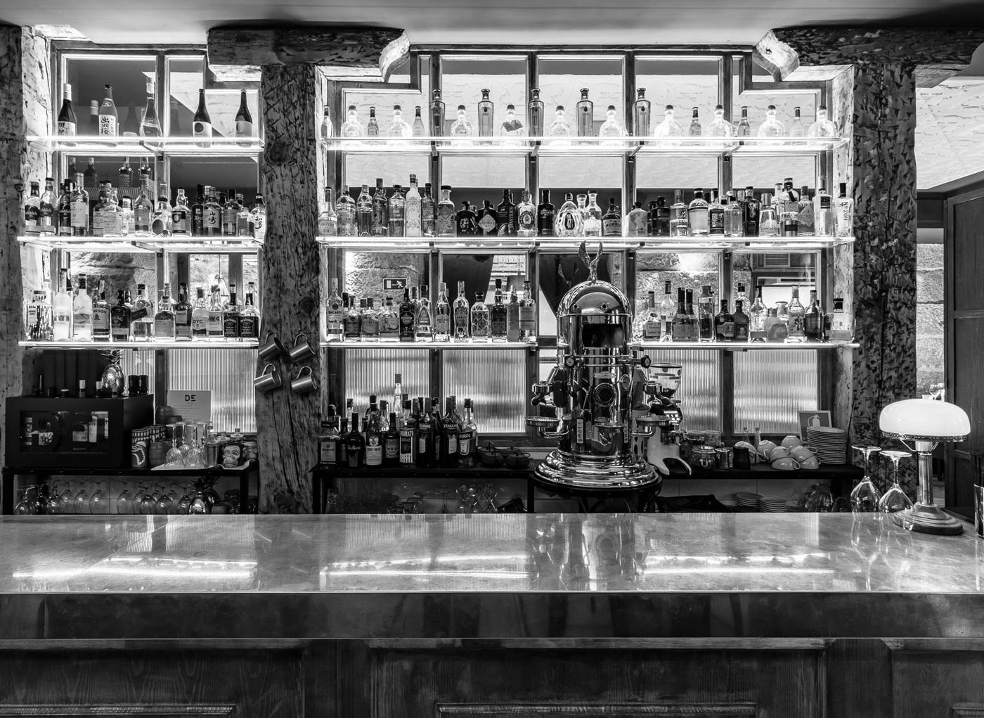 Vista de la barra de un bar con bebidas y botellas al fondo.
